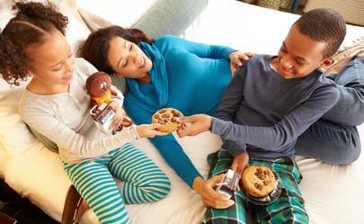 family eating cookies in bed