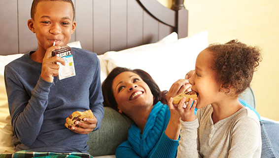 Mother and Children enoying cookies in bed