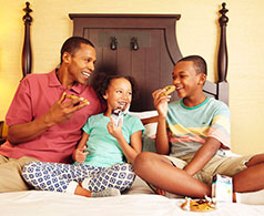 Father with his kids eating cookies on a bed in Hershey Lodge
